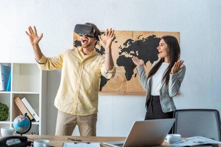 Photo pour Un agent de voyage souriant regarde un homme excité en utilisant un casque vr - image libre de droit