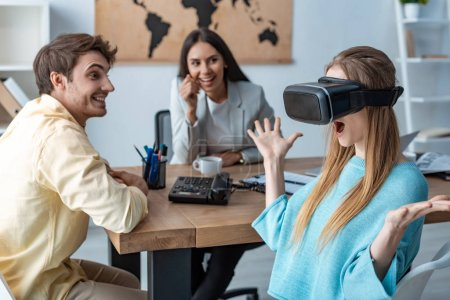 Photo for Excited girl using vr headset near boyfriend and travel agent - Royalty Free Image