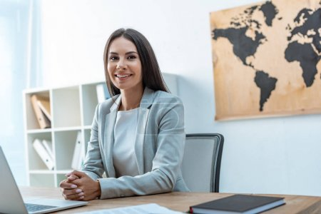 Photo for Attractive travel agent looking at camera while sitting at workplace - Royalty Free Image