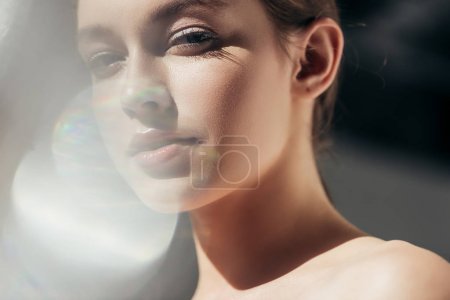 portrait of attractive nude girl on grey with lens flares