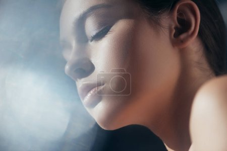 portrait of attractive tender girl on grey with lens flares