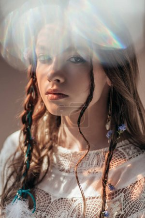 beautiful girl with braids in hairstyle posing in white boho dress on grey with lens flares