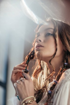 Photo for Attractive thoughtful girl with braids in hairstyle posing in white boho dress on grey with lens flares - Royalty Free Image