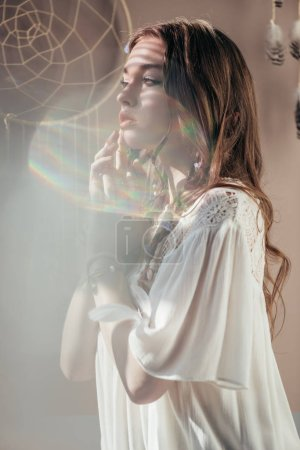 elegant girl with braids in hairstyle posing in white boho dress on grey with lens flares