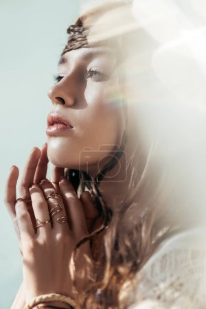 Photo for Beautiful tender girl with braids in hairstyle posing in white boho dress on grey with lens flares - Royalty Free Image