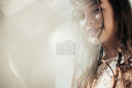 Photo for Smiling ethnic girl with braids in hairstyle posing in white boho dress on grey with lens flares - Royalty Free Image