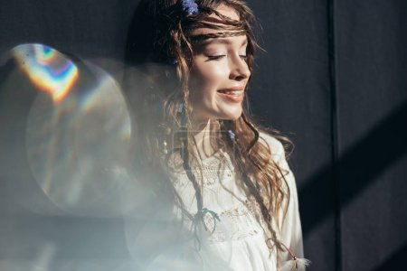 happy girl with braids in hairstyle posing in white boho dress on grey with lens flares