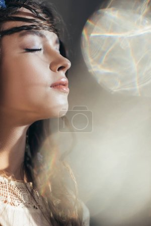 attractive boho girl with braids in hairstyle posing with closed eyes on grey with lens flares