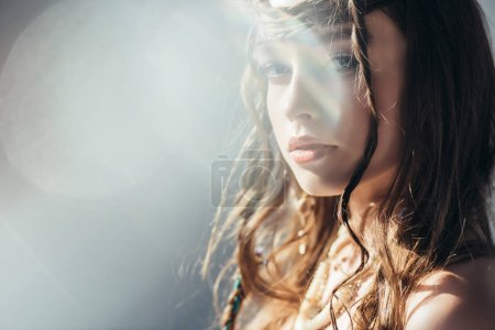 beautiful boho girl with braids in hairstyle posing on grey with lens flares