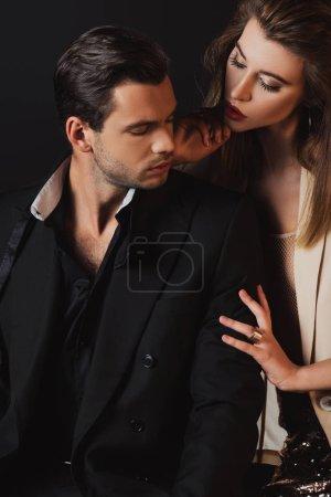 attraktive Frau umarmt gutaussehenden Mann im Anzug isoliert auf schwarz