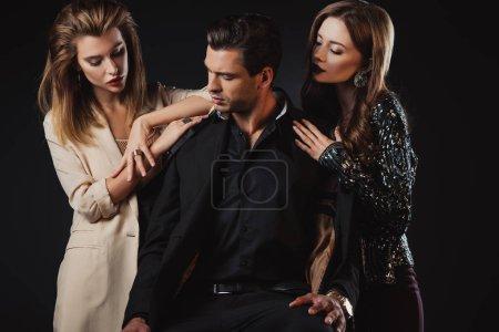 attraktive und stilvolle Frauen schöner Mann isoliert auf schwarz