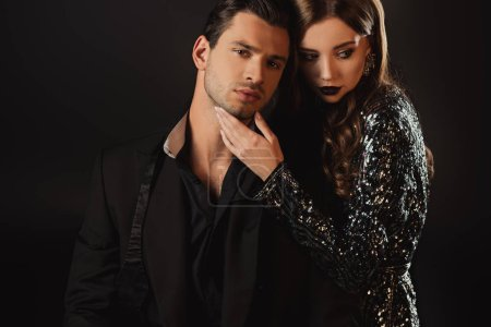 Photo pour Attrayant femme étreignant bel homme en costume isolé sur noir - image libre de droit