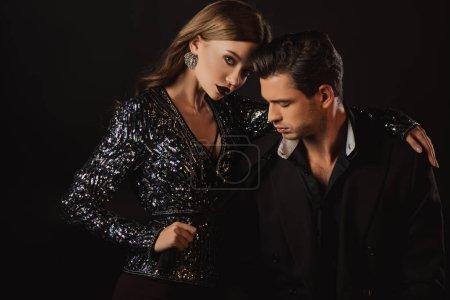Photo pour Attrayant femme étreignant et tenant cravate de bel homme en costume isolé sur noir - image libre de droit