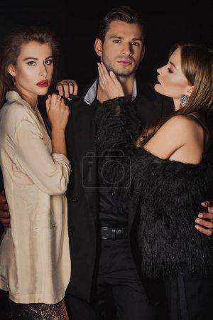 Photo pour Attrayant et élégant femmes étreignant bel homme isolé sur noir - image libre de droit