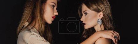 Foto de Foto panorámica de mujeres atractivas y elegantes que se miran unas a otras aisladas en negro. - Imagen libre de derechos