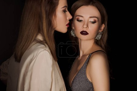 Photo pour Attractive and stylish woman looking at her friend isolated on black - image libre de droit