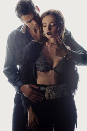 Photo pour Bel homme étreignant femme attrayante en soutien-gorge isolé sur blanc - image libre de droit