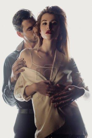 Photo pour Bel homme étreignant et embrassant jolie femme isolée sur blanc - image libre de droit