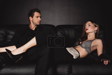 Photo for Attractive woman lying on sofa and handsome man looking at her on black background - Royalty Free Image