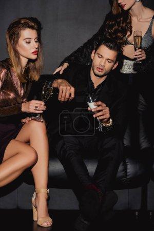 Photo pour Bel homme versant du champagne pour des femmes chic et séduisantes isolées sur le noir - image libre de droit