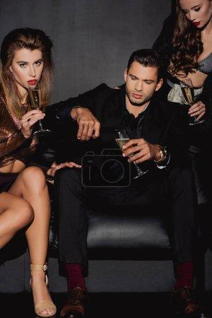 Foto de Un hombre guapo vertiendo champán para mujeres atractivas y elegantes aisladas en negro. - Imagen libre de derechos