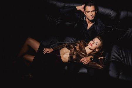 Photo pour Vue de dessus de la femme attrayante couché sur bel homme isolé sur noir - image libre de droit