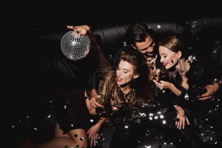 Photo pour Top view of attractive and smiling women with disco ball and handsome man with champagne glass isolated on black - image libre de droit