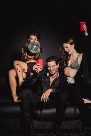 Photo pour Attractive and smiling friends holding disco ball and plastic cups on black background - image libre de droit