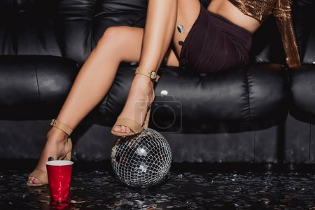 Photo pour Cropped view of woman standing on disco ball and sitting on sofa - image libre de droit
