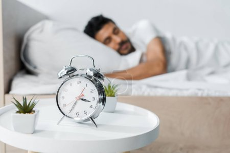 selective focus of alarm clock, plants and handsome bi-racial man sleeping on background