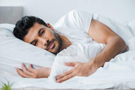 Photo pour Bel homme bi-racial couché au lit et regardant la caméra le matin - image libre de droit