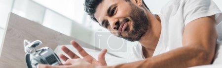 Photo pour Photo panoramique d'un homme biracial insatisfait tenant un réveil le matin - image libre de droit