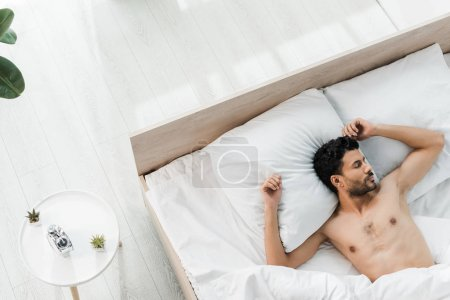 Photo for Top view of sexy and handsome bi-racial man sleeping in bed in morning - Royalty Free Image