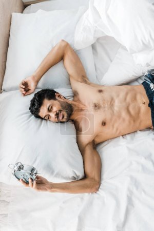 Photo pour Top view of sexy and handsome bi-racial man sleeping in bed in morning. - image libre de droit