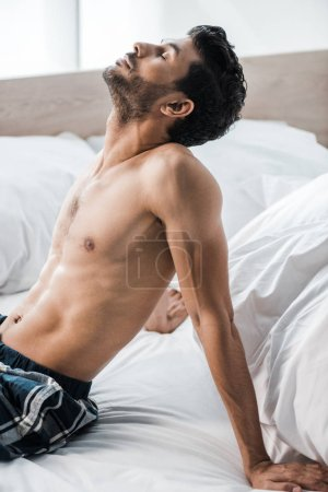 Photo for Handsome and sexy bi-racial man sitting on bed in morning - Royalty Free Image