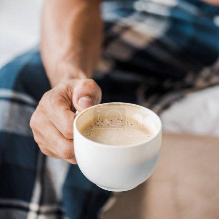 Photo pour Vue recadrée de l'homme bi-racial tenant une tasse de café le matin - image libre de droit