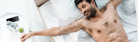 Photo for Panoramic shot of handsome bi-racial man waking up and stretching in morning - Royalty Free Image