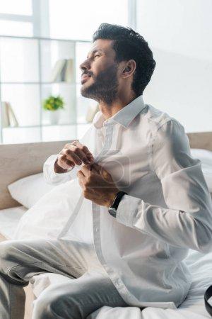 Photo pour Bel homme bi-racial s'habillant et s'asseyant sur le lit le matin - image libre de droit
