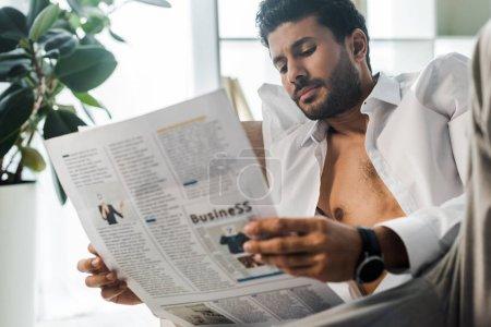 Photo pour Foyer sélectif de beau bi-racial homme lecture journal le matin - image libre de droit