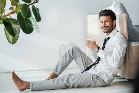 schöner und lächelnder Geschäftsmann mit einer Tasse Kaffee am Morgen