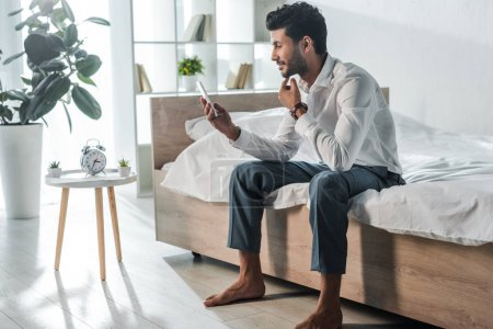 handsome and smiling bi-racial businessman using smartphone in morning at home