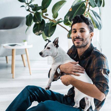 Photo pour Homme bi-racial souriant et beau tenant Jack Russell Terrier - image libre de droit