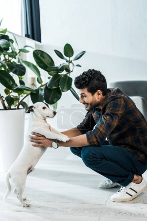 Photo pour Side view of handsome and smiling bi-racial man holding jack russell terrier - image libre de droit