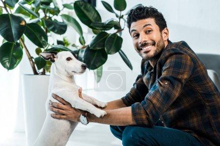 Photo pour Bel homme bi-racial souriant tenant Jack Russell Terrier - image libre de droit