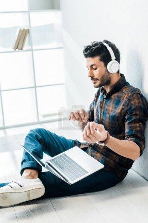 Photo pour Bel homme bi-racial avec ordinateur portable écouter de la musique et imiter jouer à la guitare - image libre de droit