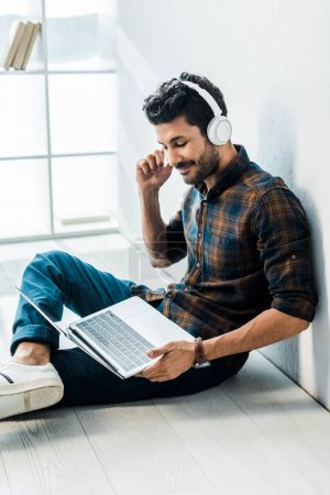 handsome and smiling bi-racial man with laptop listening music