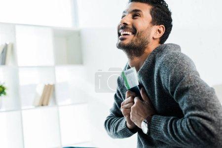 Photo pour Bel homme bi-racial souriant en pull avec passeport et billet d'avion - image libre de droit