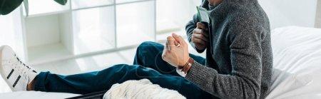 Photo pour Prise de vue panoramique de l'homme bi-racial en pull tenant un passeport avec billet d'avion et montrant un geste oui - image libre de droit