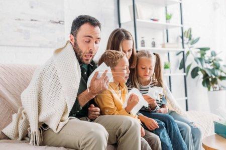 Photo pour Famille malade, enveloppée dans une couverture, assise sur le canapé et éternuant dans des serviettes - image libre de droit