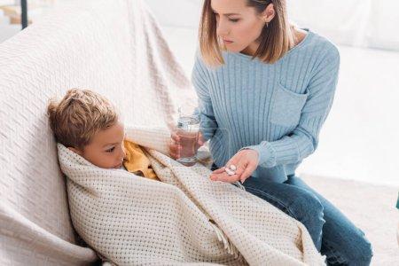 Photo pour Mère attentive donnant des médicaments à son fils malade enveloppé dans une couverture - image libre de droit